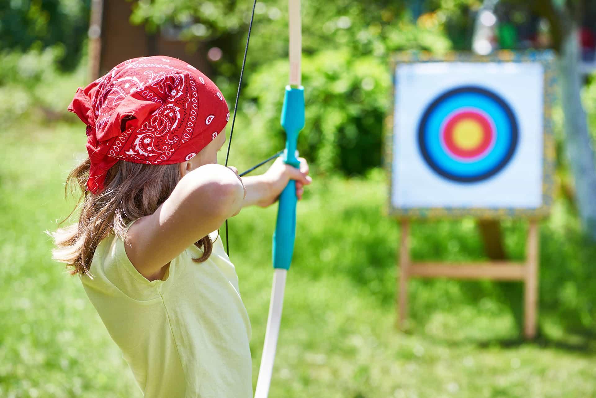 Ett barn skjuter med pilbåge i trädgården