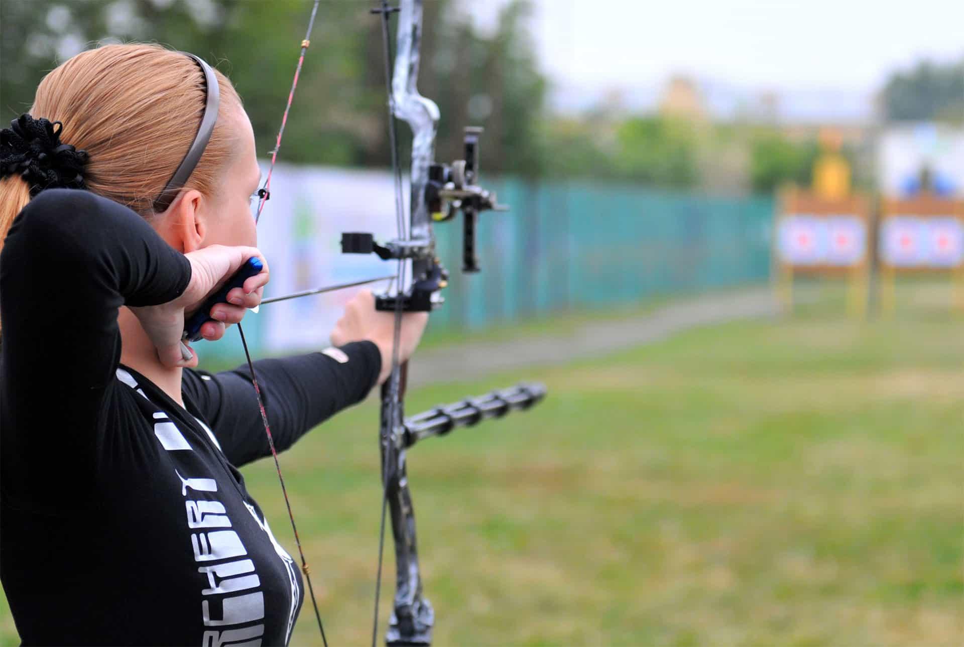 En kvinna med profilkläder förebreder sig för att skjuta en pil på en måltavla