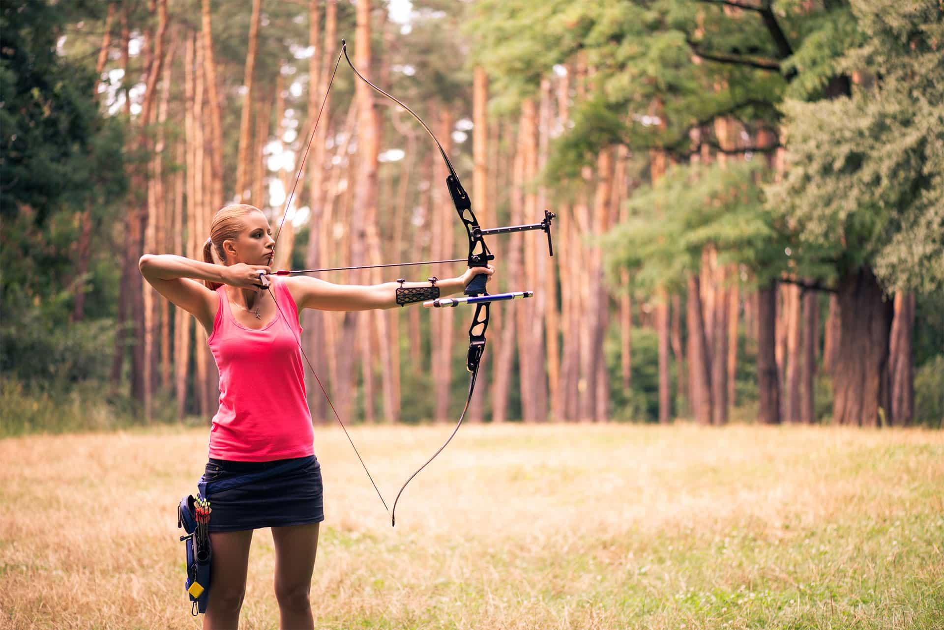 Kvinna i rosa kläder övar pilbågskytte i en skogsdunge